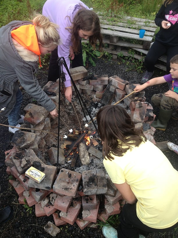Kids melting marshmallows on fire